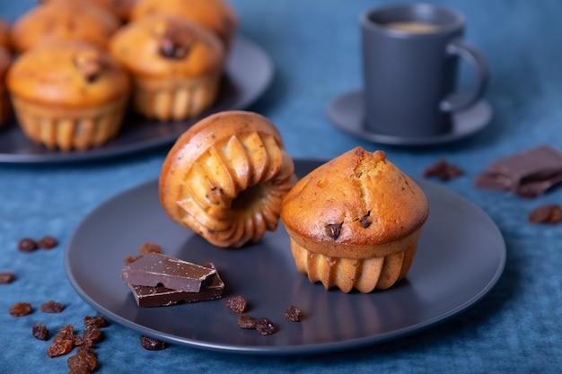 チョコレートとレーズンのマフィン。自家製のベーキング。マフィンと一杯のコーヒーのプレート。