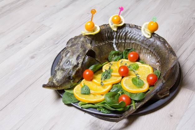 オレンジ、ほうれん草、チェリートマト、サイサリスのチョウザメ。全体を焼きました。セレクティブフォーカス。