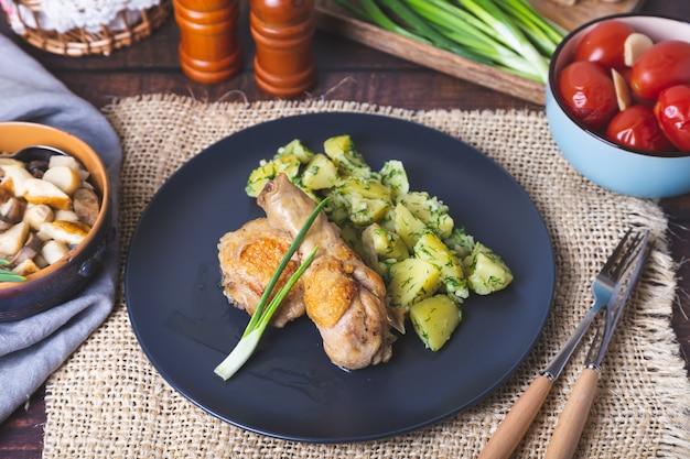 Курица с картофелем, солеными помидорами и маринованными грибами. на заднем плане солонка с луком и чесноком. деревенский стиль