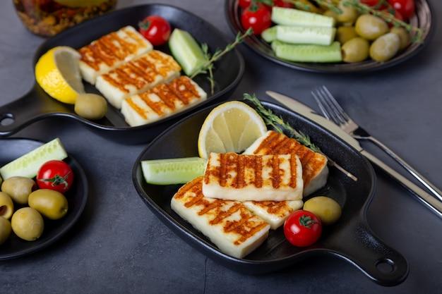 Сыр халуми на гриле на черной сковороде с оливками, помидорами, огурцами и пепперони. крупный план.