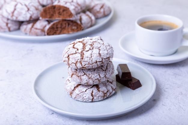 粉砂糖とコーヒーカップをまき散らした割れたチョコレートクッキー