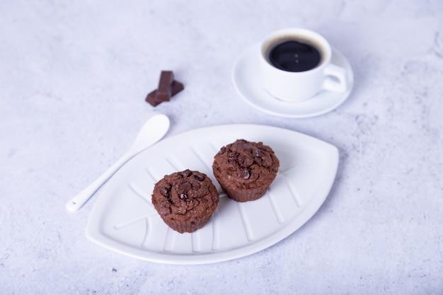 白い皿にチョコレートのマフィン。自家製のベーキング。背景には一杯のコーヒーがあります。白色の背景。セレクティブフォーカス、クローズアップ。
