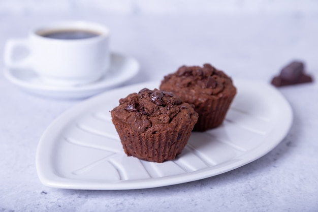 Шоколадные маффины на белом фоне. домашняя выпечка. на заднем плане чашка кофе. белый фон. выборочный фокус, крупным планом.