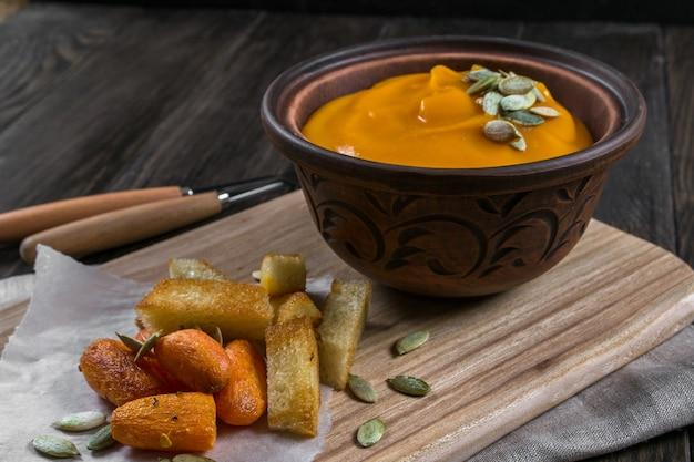 粘土のボウルにカボチャのクリームスープ、スナック揚げクルトンパン、暗い木製のテーブルで焼きたてのニンジン