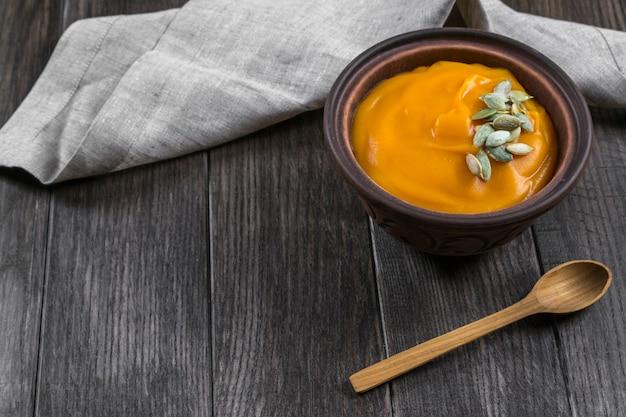 暗い木製のテーブルの上に粘土ボウルに種を入れたカボチャのクリームスープ