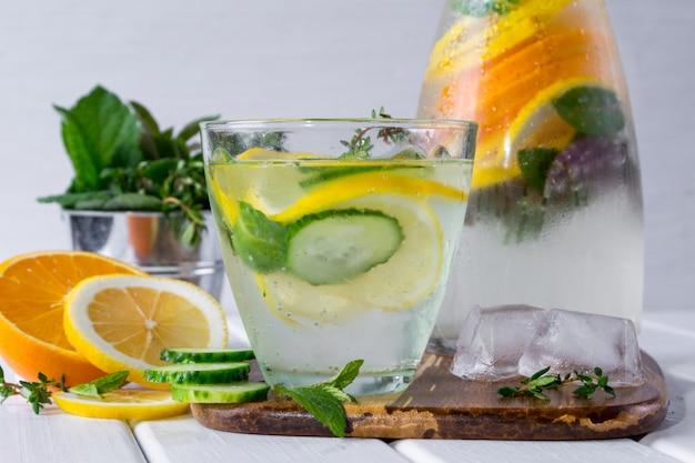 Минеральная вода с дольками лимона и мяты на белой деревянной поверхности