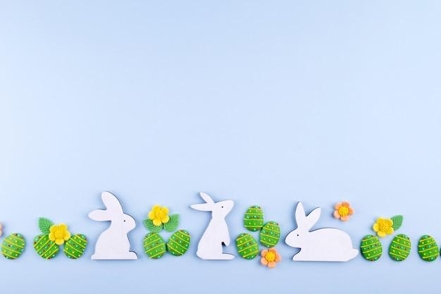 Пасхальный праздник фон. зеленый сахар конфеты яйца, кролик на синем фоне. плоская планировка, вид сверху
