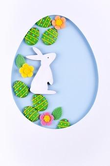 紙、砂糖菓子の卵、青の背景にバニーで作られたイースターエッグフレーム