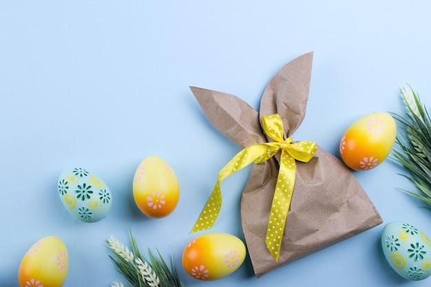 Пасхальная композиция с крафт-бумагой в виде зайчика, разноцветных пасхальных яиц и цветов. плоская планировка, копирование пространства