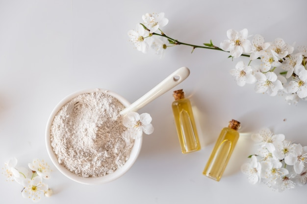 白い表面に白い粘土粉末を使ったセラミックボウル。自家製のフェイシャルとボディマスクまたはスクラブ、開花チェリーの新鮮な小枝の成分。スパとボディケアのコンセプトです。