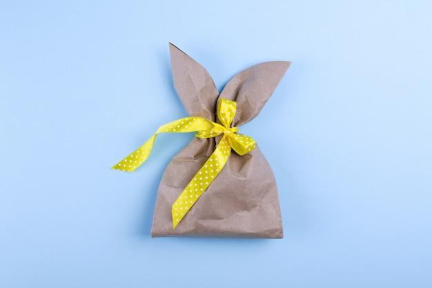 Праздник пасхи фон с ремеслом бумажный пакет в форме кролика. вид сверху