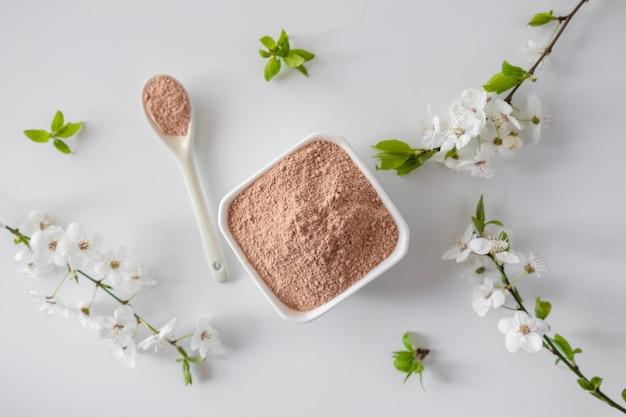 赤い粘土の粉末が入ったセラミックボウル。自家製のフェイシャルとボディマスク、またはスクラブと白い表面に開花桜の新鮮な小枝を。スパとボディケアのコンセプトです。