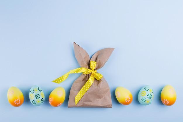 卵とイースター休日の背景。カラフルな塗装鶏の卵とウサギの形をしたクラフトペーパーパッケージの平面図