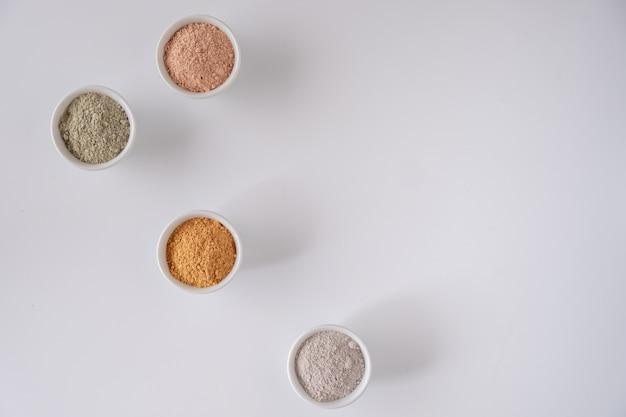 Набор различных косметических глиняных порошков на белой поверхности