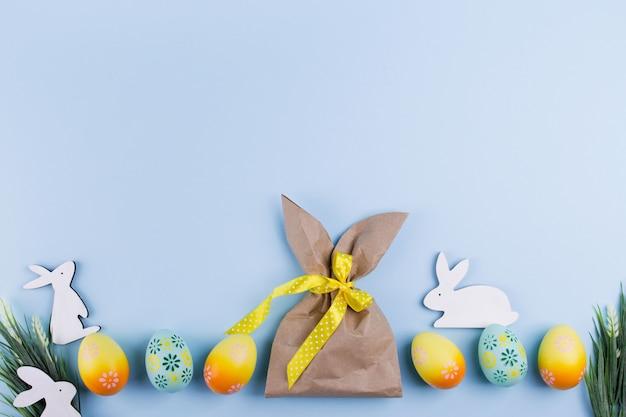 イースターの休日の背景バニーの形をした行とクラフト紙のパッケージに編まれたカラフルな塗装鶏の卵の平面図