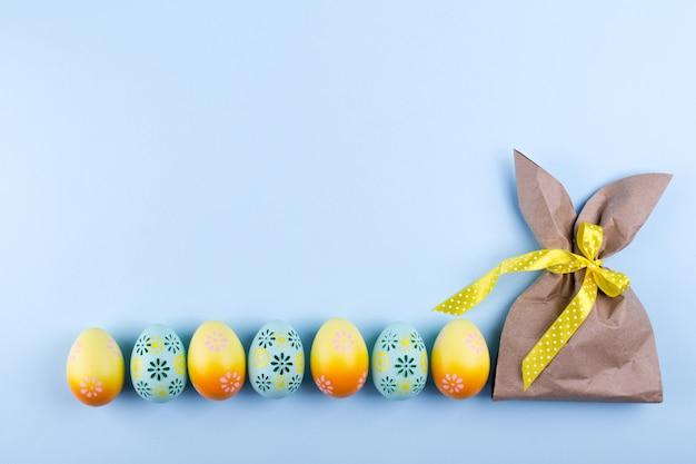 Пасхальный фон праздник вид сверху разноцветных крашеных куриных яиц и крафт-бумаги в виде зайчика