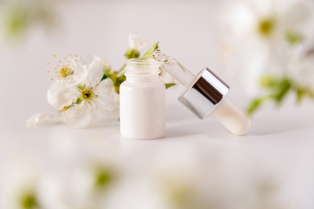白い表面に白い化粧品スキンケアドロッパーボトル包装桜の花