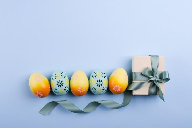 Пасхальный праздник фон вид сверху разноцветных окрашенных куриных яиц, размещенных в ряд и настоящее окно с лентой