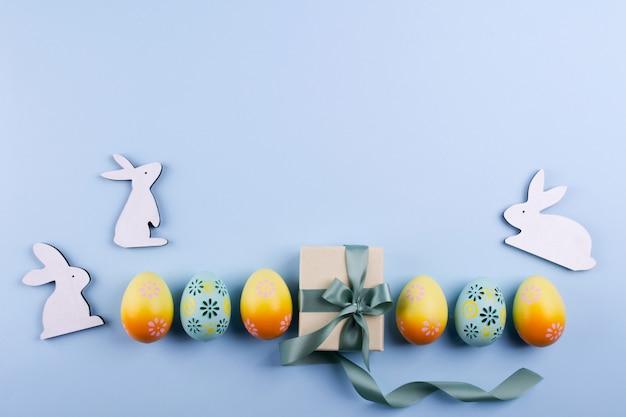 Пасхальный праздник фон вид сверху красочные расписные куриные яйца и настоящее окно с лентой