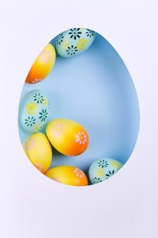 紙で作られたイースターフレーム、青の背景にカラフルな塗装鶏の卵。イースターの構成。平干し、コピースペース