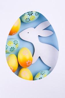 Пасхальная рама изготовлена из бумаги, красочные окрашенные куриные яйца, белый деревянный кролик на синем фоне. пасхальная композиция. плоская планировка,