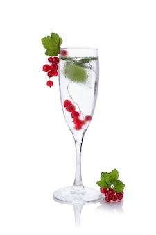 シャンパングラスで白で隔離赤いスグリと水のさわやかなガラス
