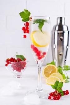 Свежий лимонад с лимоном и красной смородиной на белом фоне