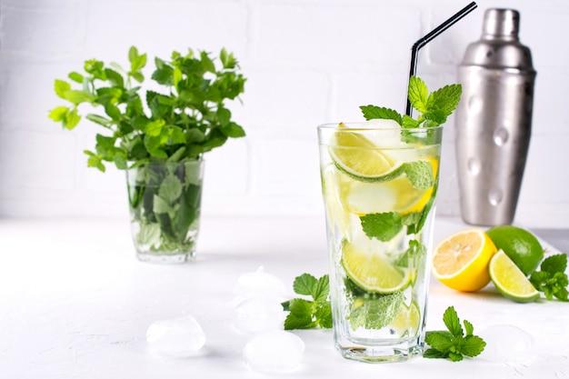 Летний освежающий коктейль с мятой и лаймом со льдом в стакане, свежими ингредиентами и шейкер