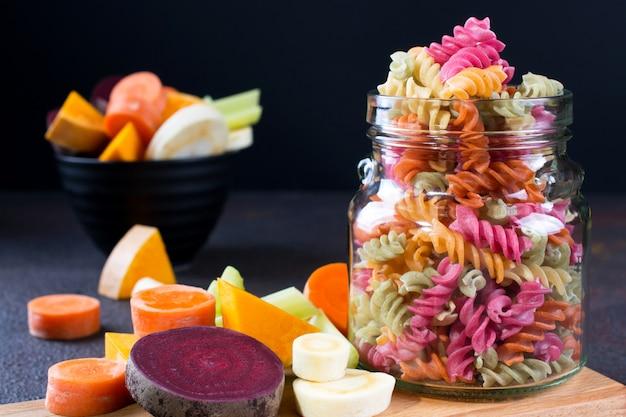 Рис фузилли сухая паста из овощей в стеклянной банке. его натуральные растительные красители сельдерей, свекла, морковь, тыква, пастернак. концепция здорового питания без глютена