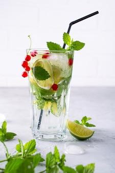 Холодный летний напиток, сангрия, лимонад или мохито со свежим лимоном из красной смородины, листьями мяты лайма с ингредиентами.