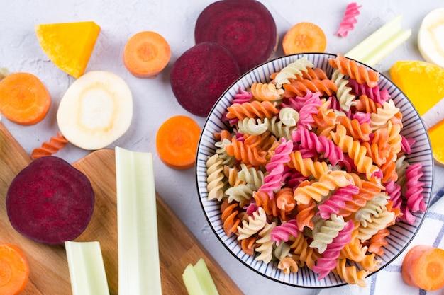 Фон из ярких красочных сухих макаронных изделий из овощей и натуральных растительных красителей из сельдерея, свеклы, моркови, тыквы, пастернака. концепция здорового питания