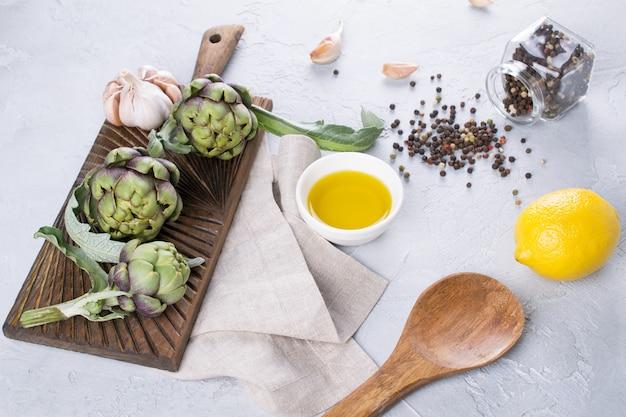 Свежие спелые зеленые артишоки на разделочной доске готовы приготовить и ингредиенты чеснок, лимон и оливковое масло