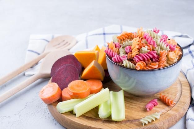 Концепция здорового питания без глютена. рисовая фузилли сухая паста из овощей в серой керамической миске и натуральные растительные красители из сельдерея, свеклы, моркови, тыквы, пастернака.