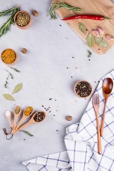 テクスチャの灰色の背景にハーブとスパイスが香る木製スプーン。食品フラットが横たわっていた。