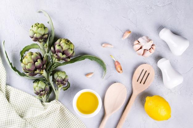 Зеленые спелые сырые артишоки головы готовы приготовить. артишоки и ингредиенты чеснок, лимон и оливковое масло
