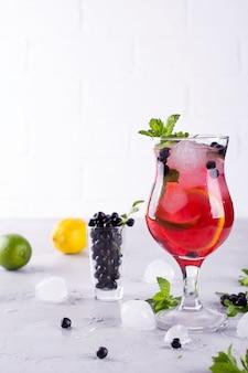 Летний холодный напиток с черникой, мятой, лимоном и льдом в стакане