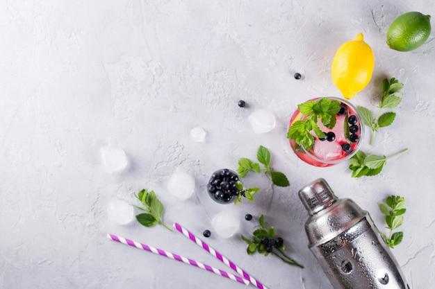 Ингредиенты для приготовления лимонада, коктейлей мохито или других напитков с черникой на сером бетонном фоне