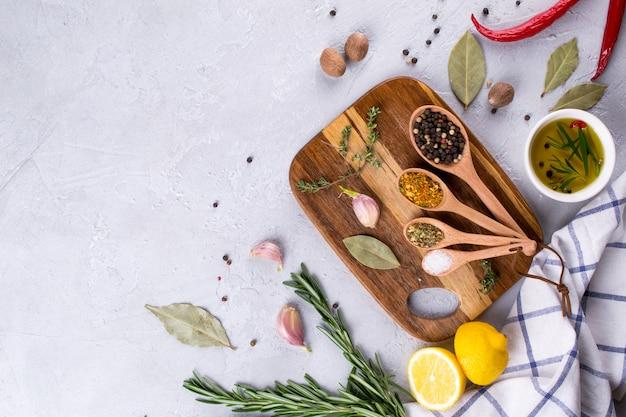 Разделочная доска с зеленью и специями - розмарин, чеснок, соль, перец, оливковое масло, лимон. кулинарный фон. продовольственная квартира лежала.