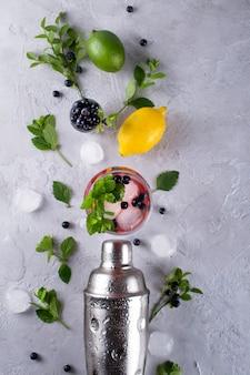 Шейкер, лимон, лайм, листья мяты черника и лед для приготовления летнего коктейля