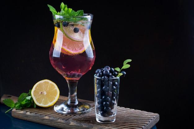 Холодный летний домашний фруктово-ягодный лимонад. мохито, лимонад или сангрия в стакане. на темном фоне