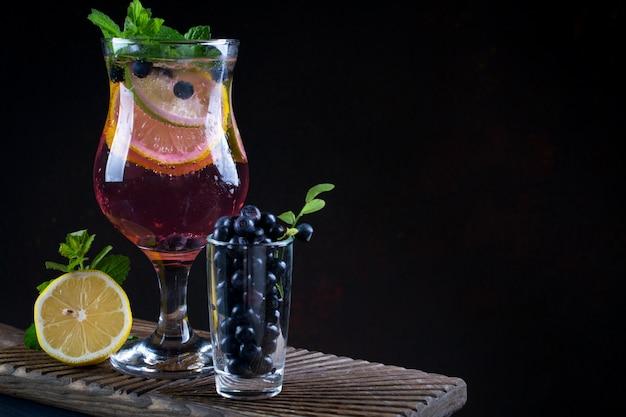 Свежий черничный летний мохито коктейль. черничный лимонад или сангрия на темном фоне