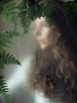 Молодая женщина с завитками за мокрым стеклом с зелеными листьями