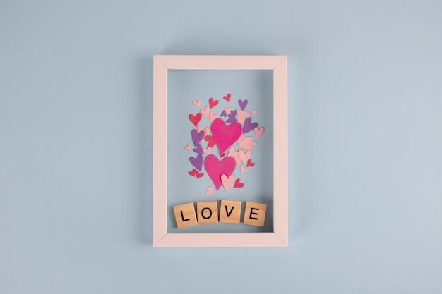 木製のキューブと青いテーブルの上の心の愛という言葉