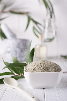 Сухая лицевая глина в миске. натуральная косметика для дома или салона санаторно-курортное лечение на белом фоне