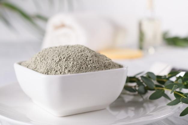 Маска грязи мертвого моря, порошок марокканской глины, ингридиенты продуктов красоты на белой предпосылке.