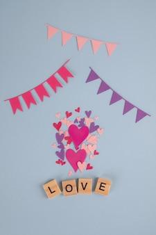 木製キューブ、花輪、青いテーブルの心で愛という言葉