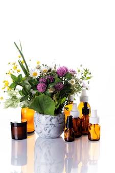 Полевые цветы в мраморной ступке и лекарства стеклянной бутылке на белом