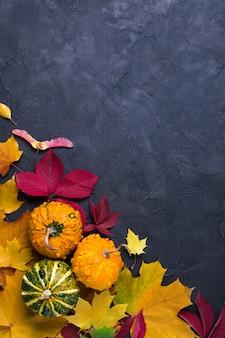 秋の組成物。異なる多色乾燥葉と暗い背景にカボチャで作られたフレーム。秋、秋のコンセプトです。フラット横たわっていた、トップビュー、コピースペース