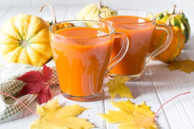 Традиционный осенний напиток. стеклянные чашки тыквенного сока, тыквы и опавших кленовых листьев