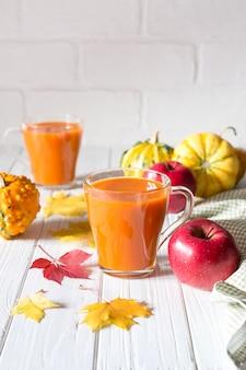 Сезонный осенний день благодарения концепции. коктейль питья свежего сока тыквы на белой таблице с кленовыми листами падения. копировать пространство
